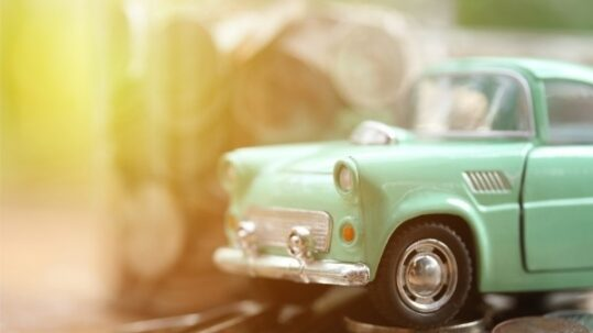 A toy classic car and coins