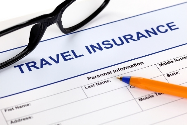 Travel insurance form with glasses and pen