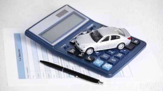 Toy car, car insurance documents and calculator on table