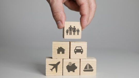 Hand arranging wooden blocks with car insurance, house insurance, travel insurance and boat insurance icons.