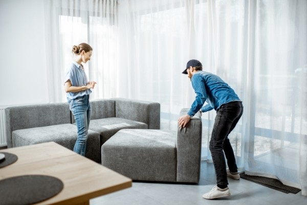 Delivery man moving a new sofa for a young woman client in the modern apartment