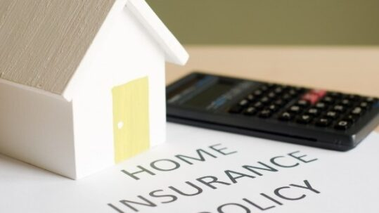 Home insurance document, calculator and toy house on table